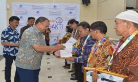 Penyerahan bingkisan kepada para purnabakti oleh Direktur Utama BAKTI Anang Latif pada acara Pelepasan Purnabakti Kominfo (28/12).